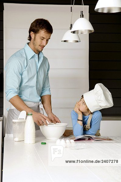 Ein erwachsener Mann macht einen Kuchen und sein Sohn in der Küche. Ein erwachsener Mann macht einen Kuchen und sein Sohn in der Küche.