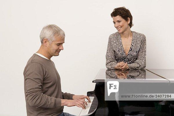 Ein reifer Mann  der Klavier spielt  und eine erwachsene Frau  die in seiner Nähe steht.