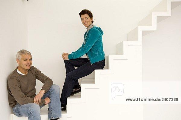 Porträt eines reifen Mannes und einer mittleren erwachsenen Frau  die auf einer Treppe sitzt.