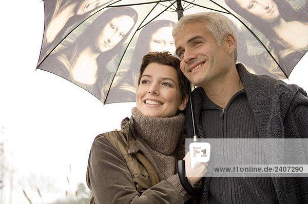 Nahaufnahme einer mittleren erwachsenen Frau und eines reifen Mannes unter einem Regenschirm