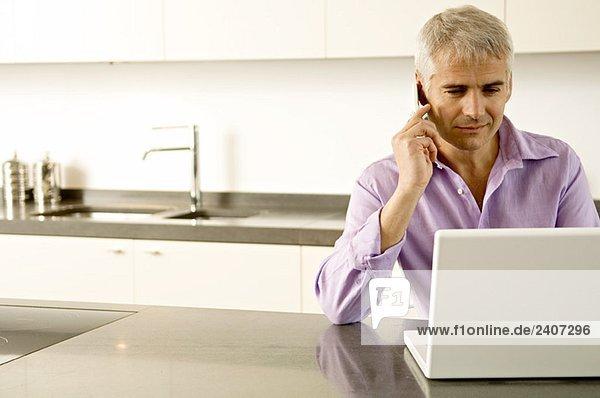 Älterer Mann  der am Laptop arbeitet  während er mit dem Handy spricht