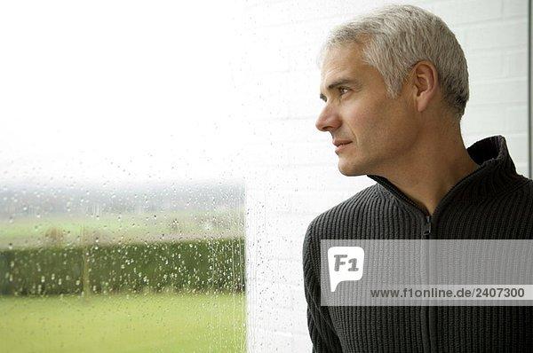 Nahaufnahme eines reifen Mannes mit Blick aus dem Fenster