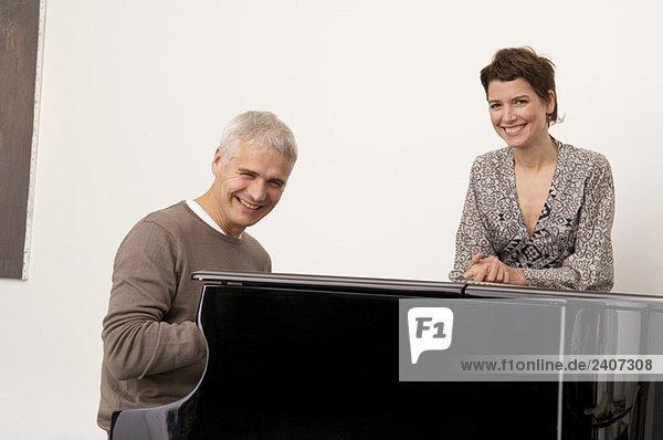 Porträt eines reifen Mannes am Klavier und einer erwachsenen Frau in seiner Nähe
