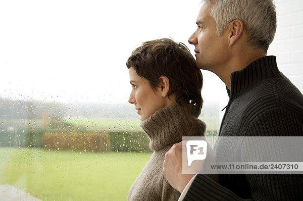 Mittlere erwachsene Frau und ein reifer Mann  der aus dem Fenster schaut.