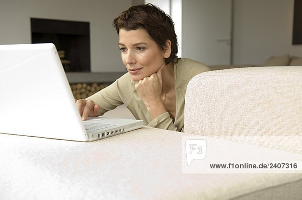 Mid adult woman working on a laptop in a living room