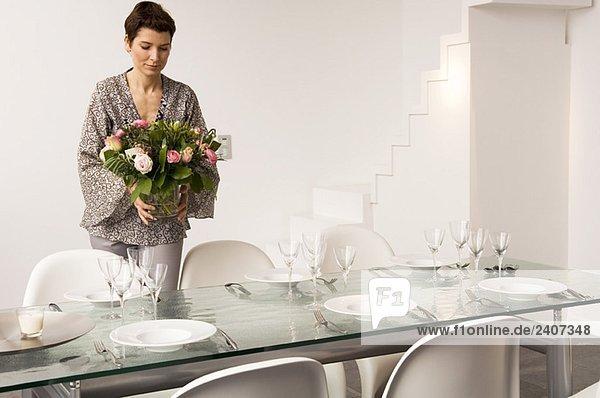 Mittlere erwachsene Frau  die einen Esstisch deckt