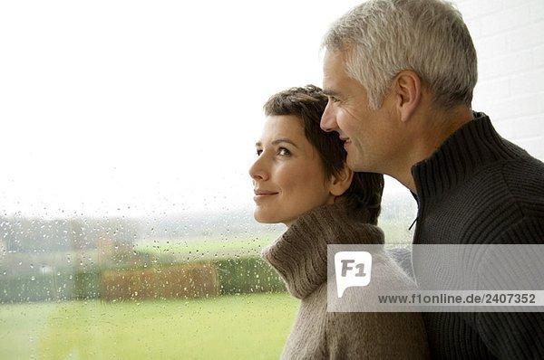 Mittlere erwachsene Frau und ein reifer Mann stehen am Fenster