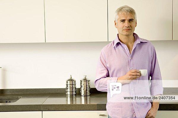 Porträt eines reifen Mannes mit einer Tasse Tee in der Küche