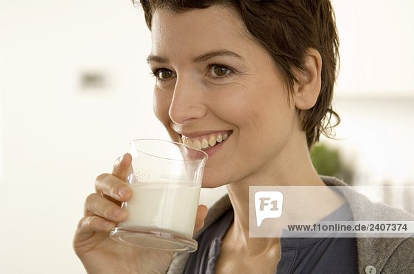 Close-up of a mid adult woman drinking a glass of milk