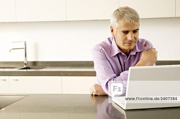 Erwachsener Mann mit einem Laptop in der Küche Erwachsener Mann mit einem Laptop in der Küche