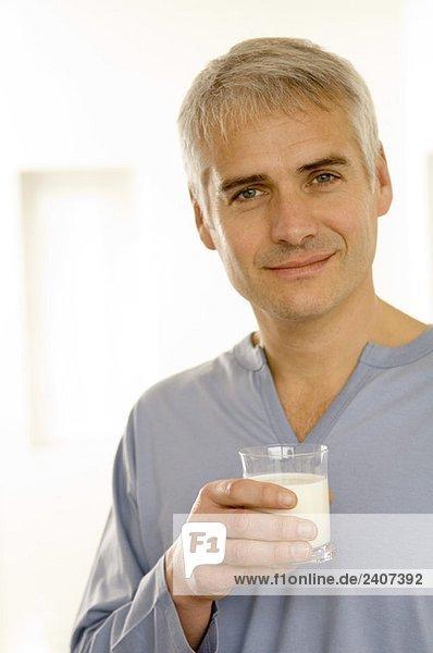 Porträt eines reifen Mannes mit einem Glas Milch