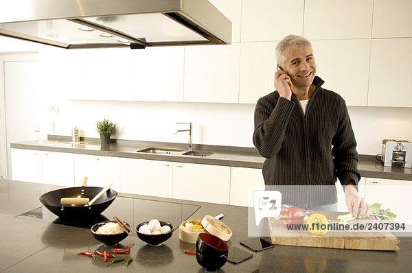 Porträt eines reifen Mannes  der auf einem Handy in der Küche spricht.