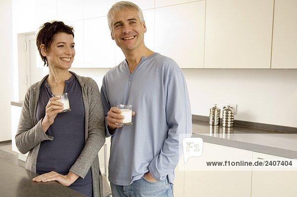 Ein reifer Mann und eine erwachsene Frau mit Milchgläsern.