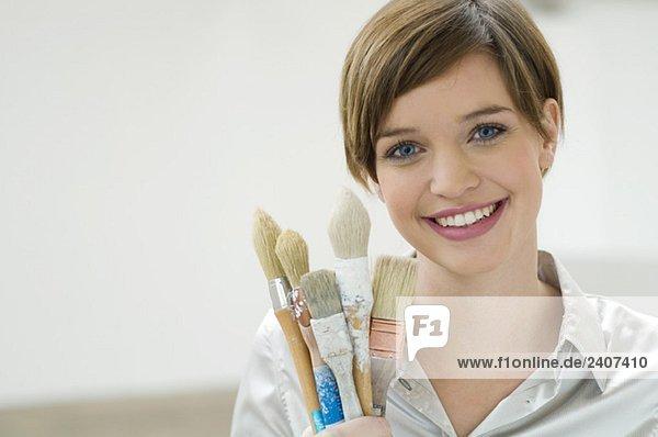 Porträt einer jungen Frau mit Pinseln