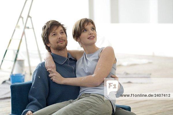Junge Frau sitzt auf dem Schoß eines erwachsenen Mannes.