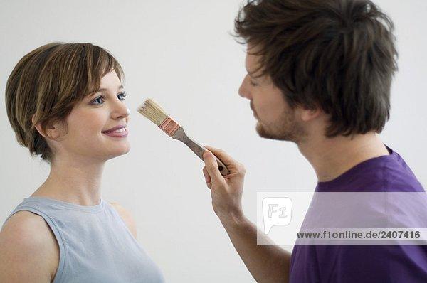 Nahaufnahme eines erwachsenen Mannes  der Farbe auf die Nase einer jungen Frau aufträgt.