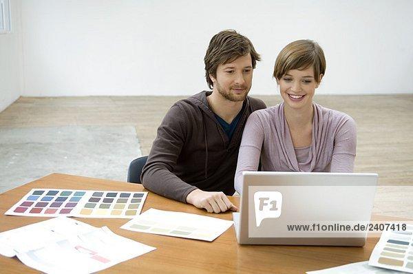 Mid Erwachsenen Mann und eine junge Frau mit einem Laptop und lächeln