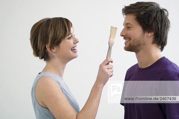 Junge Frau hält einen Pinsel vor das Gesicht eines erwachsenen Mannes.