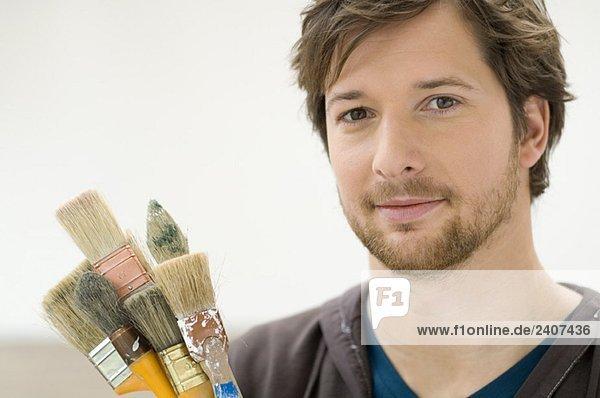 Porträt eines erwachsenen Mannes mit Pinseln