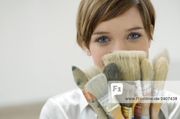 Porträt einer jungen Frau mit Pinsel vor dem Gesicht