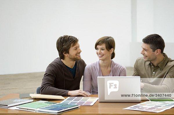 Ein erwachsener Mann und eine junge Frau diskutieren mit einem Innenarchitekten.