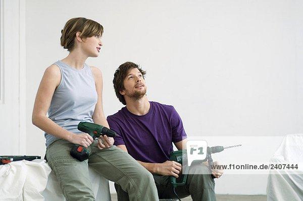 Mittlerer erwachsener Mann und eine junge Frau  die in einem Raum sitzen und Bohrer halten