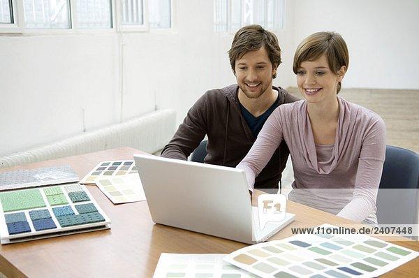 Mittlerer Erwachsener Mann und eine junge Frau mit einem Laptop