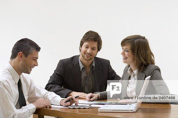 Immobilienmaklerin im Gespräch mit einem erwachsenen Mann und einer jungen Frau