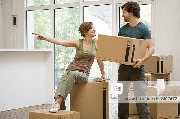 Mittlerer erwachsener Mann mit einem Karton und einer jungen Frau  die wegzeigt.