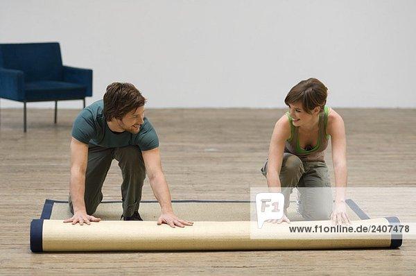 Paar Abrollen eines Teppichs auf einem Hartholzboden