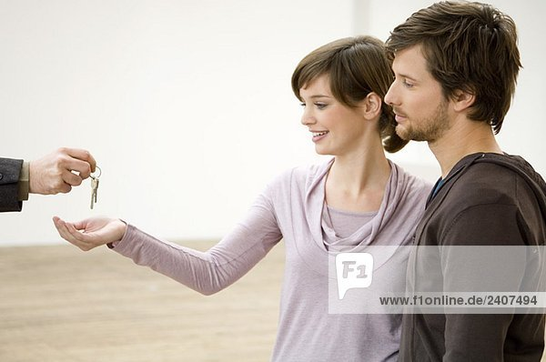 Nahaufnahme der Schlüsselübergabe eines Immobilienmaklers an ein Ehepaar