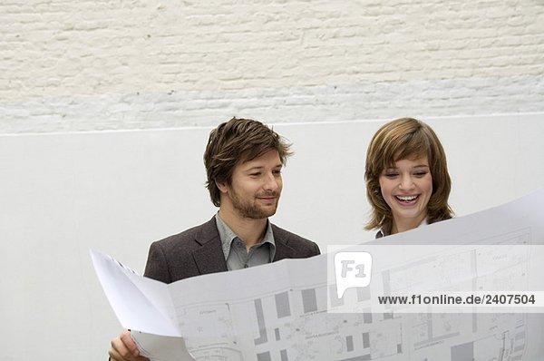 Ein erwachsener Mann und eine junge Frau  die sich einen Plan ansehen.