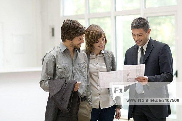 Immobilienmakler  der einem Paar einen Plan zeigt.