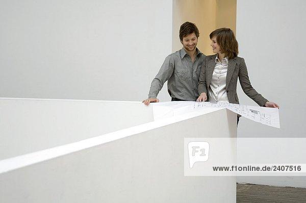 Mittlerer erwachsener Mann  der auf eine Blaupause schaut und lächelt  mit einer jungen Frau  die neben ihm steht.