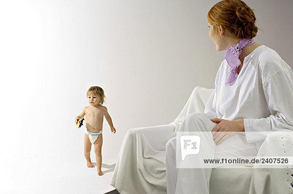 Junge Frau sitzt auf einer Couch und schaut ihren Sohn mit einem Spielzeugauto an.