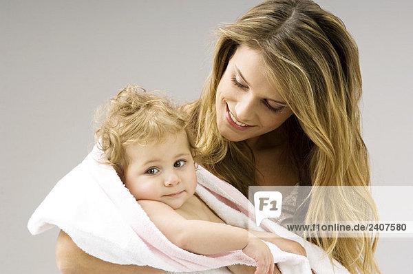 Nahaufnahme einer jungen Frau  die ihren Sohn in ein Handtuch wickelt und lächelt.