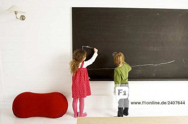 Zwei Kinder malen auf einer Tafel