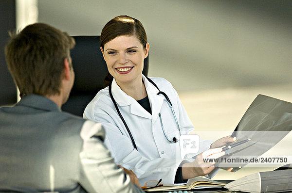 Ärztin  die einem Patienten einen Röntgenbericht zeigt
