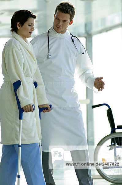 Männlicher Arzt  der einer Patientin beim Gehen auf Krücken hilft