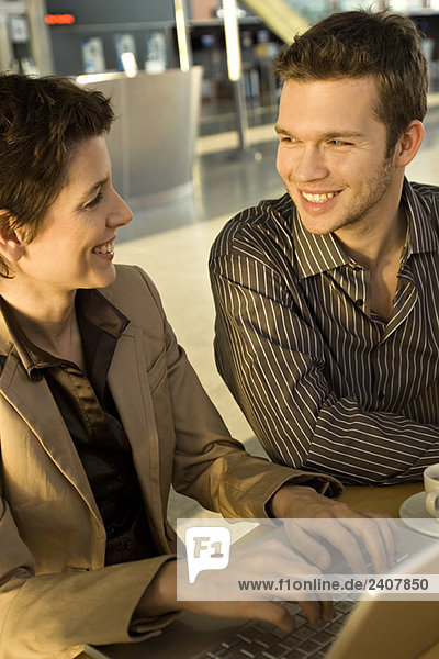 Businesswoman sitting with a businessman and smiling