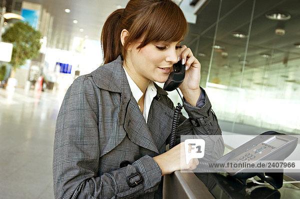 Nahaufnahme einer Geschäftsfrau am Telefon eines Flughafens
