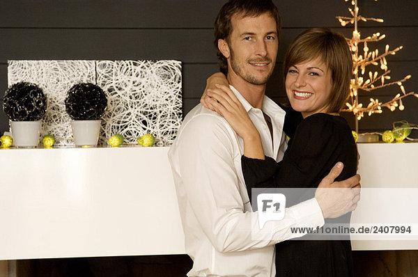 Portrait eines erwachsenen Mannes und einer jungen Frau  die sich umarmen und lächeln.