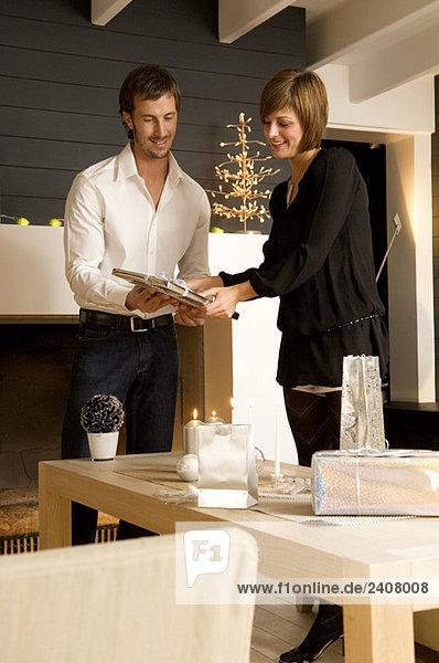 Junge Frau zeigt ein Weihnachtsgeschenk an einen erwachsenen Mann Junge Frau zeigt ein Weihnachtsgeschenk an einen erwachsenen Mann