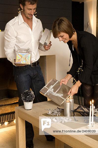 Mittlerer erwachsener Mann und eine junge Frau mit Weihnachtsgeschenken Mittlerer erwachsener Mann und eine junge Frau mit Weihnachtsgeschenken