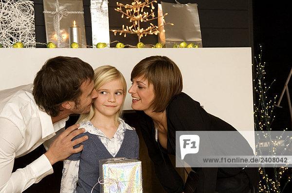 Junge Frau und ein erwachsener Mann  der ihre Tochter küsst.