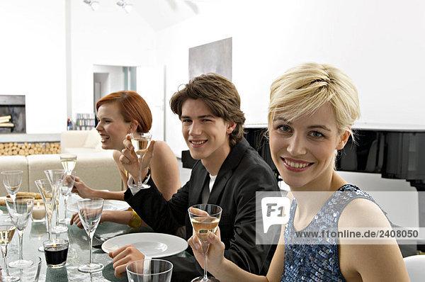 Zwei junge Frauen mit einem Teenager auf einer Dinnerparty