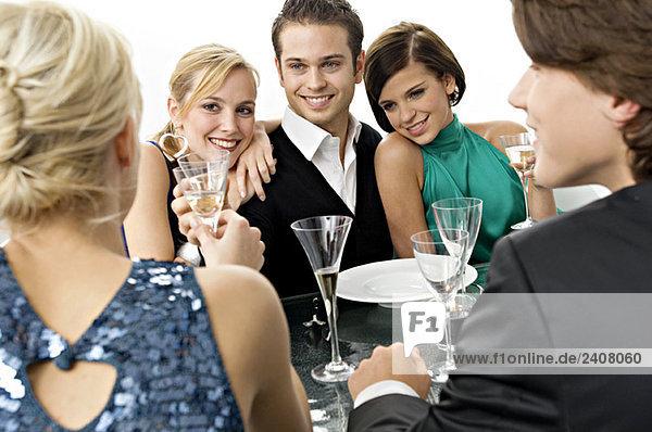 Fünf Personen genießen eine Dinnerparty