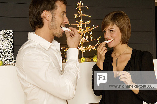 Mid adult man and a young woman eating candies