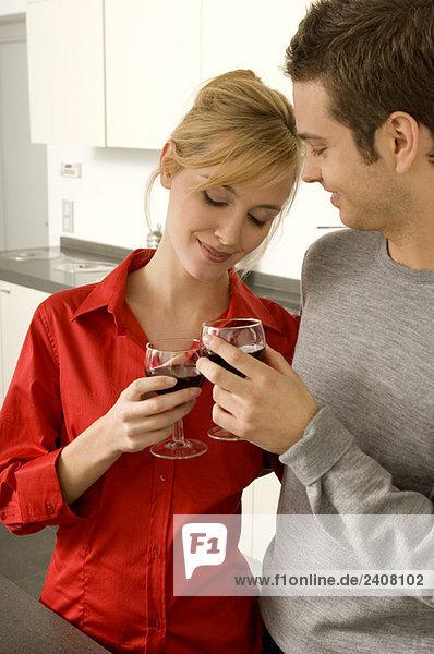 Junges Paar beim Toasten mit Weingläsern in der Küche