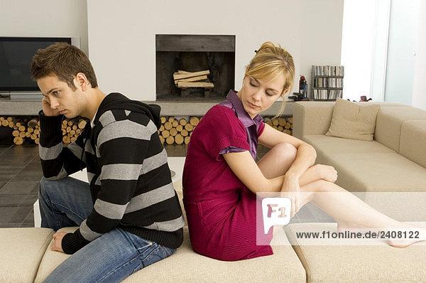 Seitenprofil eines jungen Paares  das Rücken an Rücken sitzt und ernst aussieht.
